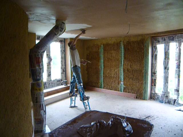 Skimming a plasterboard ceiling, on stilts, in a straw bale house