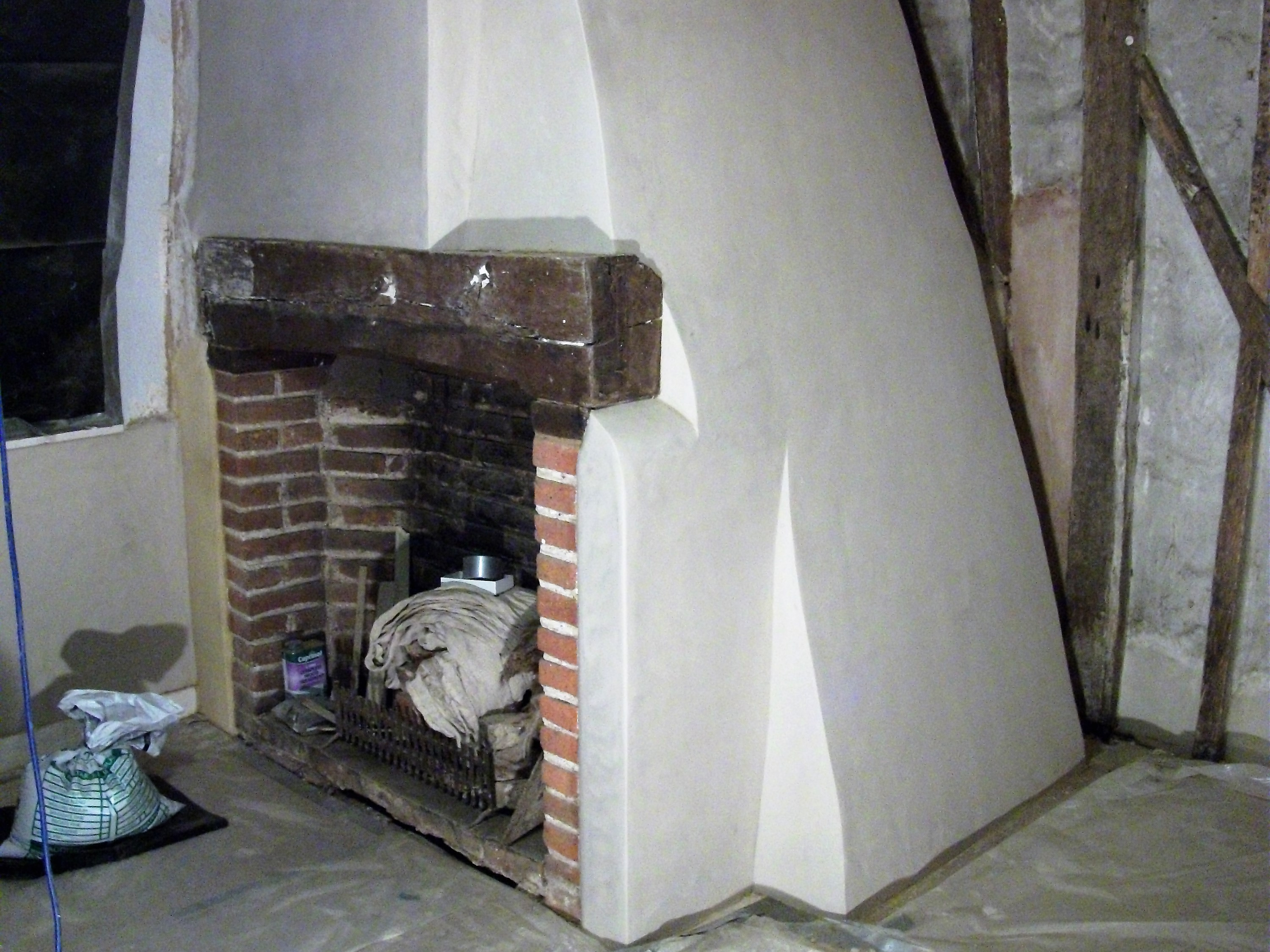 Brick fireplace plastered in lime plaster